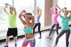 Grupo de povos de sorriso que dançam no gym ou no estúdio imagem de stock