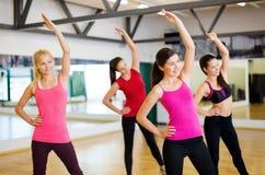 Grupo de povos de sorriso que esticam no gym Imagem de Stock