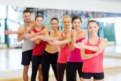 Grupo de povos de sorriso que esticam no gym Fotografia de Stock