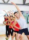 Grupo de povos de sorriso que esticam no gym Imagem de Stock Royalty Free