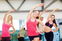 Grupo de povos de sorriso que esticam no gym Fotos de Stock Royalty Free