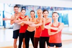 Grupo de povos de sorriso que esticam no gym Foto de Stock