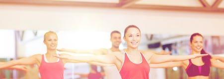 Grupo de povos de sorriso que exercitam no gym Foto de Stock Royalty Free