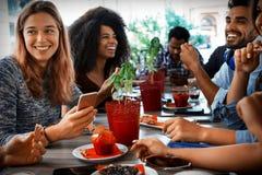 Grupo de povos diversos novos que sentam-se na tabela do restaurante que tem uma refeição junto fotos de stock royalty free