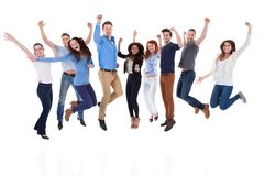 Grupo de povos diversos que levantam os braços e o salto Fotografia de Stock