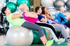 Grupo de povos novos e superiores que exercitam no gym Imagem de Stock