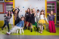 Grupo de preescolares felices que bailan en sala de juegos fotografía de archivo
