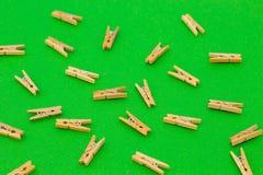 Grupo de pregadores de roupa de madeira no fundo verde Foto de Stock Royalty Free