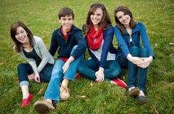 Grupo de quatro adolescentes felizes fora fotos de stock