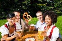 Grupo de quatro amigos em comer do jardim da cerveja   fotos de stock