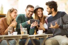 Grupo de quatro amigos que comem um café junto foto de stock royalty free