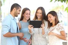Grupo de quatro amigos que olham vídeos em uma tabuleta fotos de stock royalty free