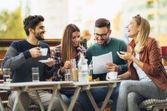 Grupo de quatro amigos que têm o divertimento um café junto imagens de stock