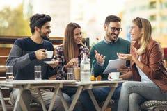 Grupo de quatro amigos que têm o divertimento um café junto  imagem de stock