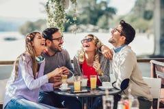 Grupo de quatro amigos que têm o divertimento um café junto fotos de stock royalty free