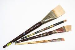 Grupo de quatro escovas de pintura espalhadas para fora imagem de stock