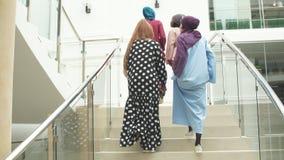 Grupo de quatro meninas muçulmanas que andam em escadas do shopping vídeos de arquivo