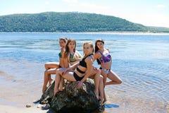 Grupo de quatro meninas no maiô na grande pedra Imagens de Stock