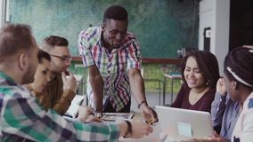 Grupo de raça misturada de arquitetos na reunião de negócios no escritório moderno Líder da equipa africano masculino que discute filme