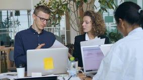 Grupo de raça misturada novo de executivos que trabalham para o projeto Start-up no escritório 4K vídeos de arquivo
