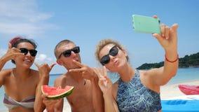 Grupo de raza mixta feliz de amigos que toman selfies y que comen la sandía fresca Veganos divertidos en la playa tailandia almacen de video