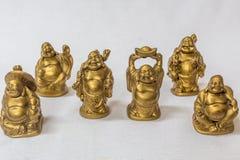 Grupo de reír a Buda pintado en color del oro en un contexto blanco Macro con la profundidad del campo extremadamente baja imagen de archivo