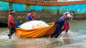 Grupo de rede dos peixes da tração do pescador Imagens de Stock Royalty Free