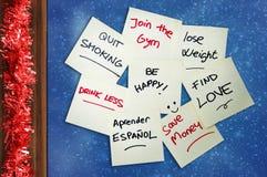 Grupo de resoluciones del Año Nuevo escritas en pila de las notas de post-it en la malla de la Navidad del marco del vidrio de la Imágenes de archivo libres de regalías