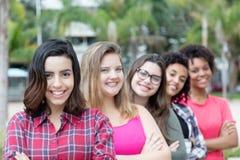 Grupo de rir as meninas internacionais que estão na linha fotografia de stock