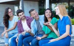 Grupo de rir homens e a mulher adultos novos foto de stock