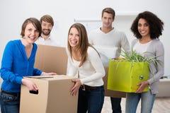Grupo de riso de amigos novos que movem a casa Fotografia de Stock