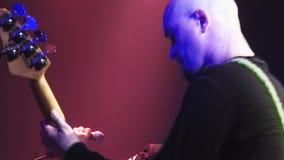 Grupo de rock Kukryniksy que executa na fase do clube noturno spotlights músicos Guitarrista Concert video estoque
