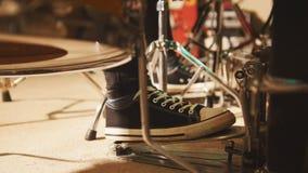 Grupo de rock que ensaia na garagem - o pé do ` s do baterista veste as sapatilhas que movem o pedal do baixo do cilindro Imagens de Stock