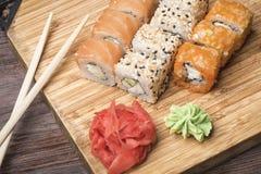 Grupo de rolos de sushi com salmões, sésamo, o caviar vermelho, o gengibre e o wasabi, varas para o sushi em uma placa de madeira Fotos de Stock Royalty Free