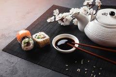 Grupo de rolos do sushi e do maki com ramo das flores brancas e do bule com o ch? verde da inscri??o na tabela de pedra imagens de stock royalty free