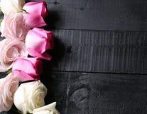 Grupo de rosas roxas, brancas e amarelas no fundo de madeira preto Imagem de Stock Royalty Free