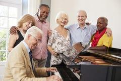 Grupo de sêniores que estão pelo piano e que cantam junto fotografia de stock
