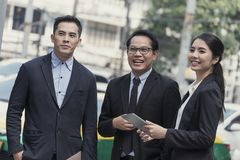Grupo de sócio asiático do negócio que discute ao andar no prédio de escritórios conceito social do colega fotografia de stock