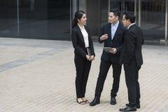 Grupo de sócio asiático do negócio que discute ao andar no prédio de escritórios conceito social do colega imagens de stock
