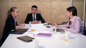 Grupo de sócios comerciais que compartilham de ideias no escritório video estoque