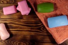 Grupo de sabão e de toalha coloridos no fundo de madeira foto de stock