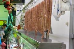 Grupo de salsichas feitos a mão que penduram em um açougue imagem de stock royalty free