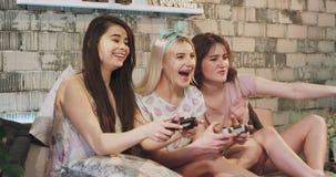 Grupo de señoras étnicas multi que jugaban en un juego de Playstation muy divertido y entusiasta concentraron al juego adentro almacen de video