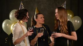 Grupo de señoras jovenes en un partido que bebe Champán y el vino que lleva los casquillos de oro y los vestidos hermosos Mujer s almacen de video