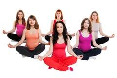 Grupo de seis mujeres embarazadas que hacen yoga Imagen de archivo