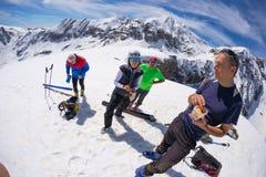 Grupo de selfie dos alpinistas na parte superior da montanha O fundo cênico da alta altitude na neve tampou cumes, dia ensolarado Imagens de Stock