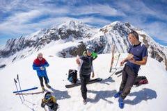 Grupo de selfie dos alpinistas na parte superior da montanha O fundo cênico da alta altitude na neve tampou cumes, dia ensolarado Foto de Stock