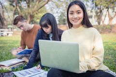 Grupo de sentada asiática de los estudiantes universitarios en la hierba verde W fotografía de archivo libre de regalías