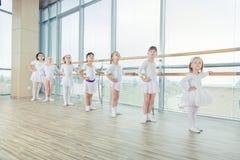 Grupo de sete bailarinas pequenas que estão na fileira e em praticar Foto de Stock Royalty Free