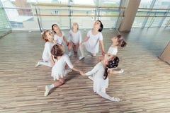 Grupo de sete bailarinas pequenas que sentam-se no assoalho São bom amigo e executores surpreendentes da dança Imagem de Stock Royalty Free